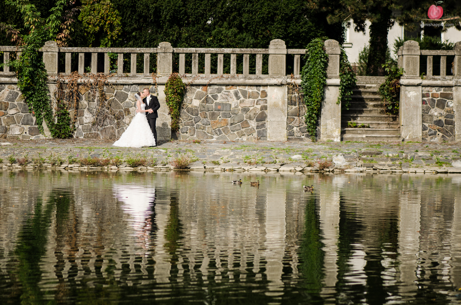 photo of bride and groom across a riverbank