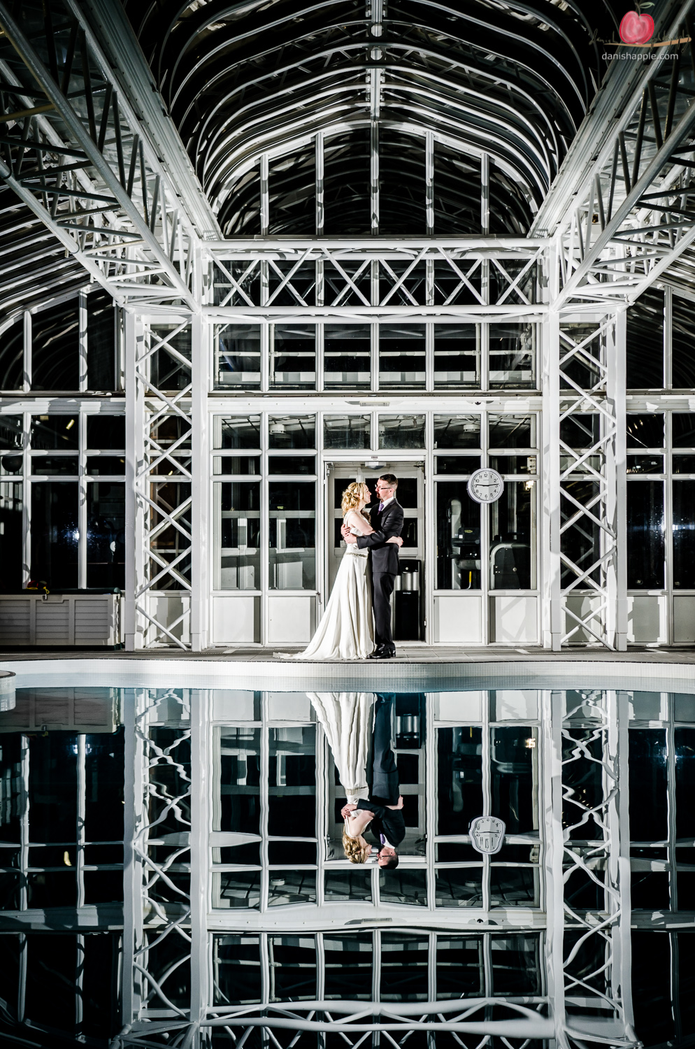 Reflection of bride and groom in swimming pool