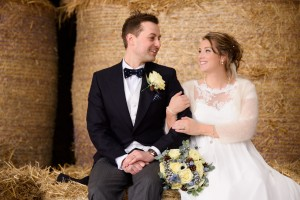 Wedding couple sat on hay bale, lit by Interfit S1 monolight